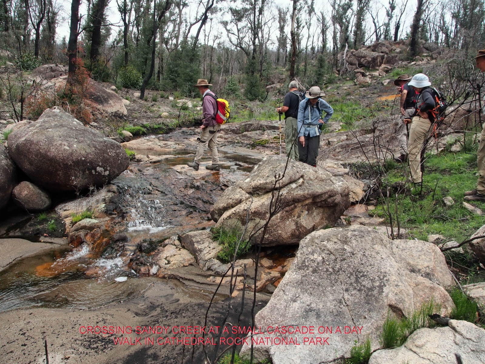 CROSSING SANDY CREEK AT A SMALL CASCADE ON A DAY WALK IN CATHEDRAL ROCK NATIONAL PARK